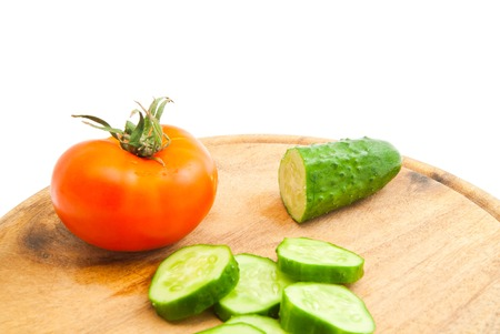 cucumber with slices and tomato on cutting board closeup
