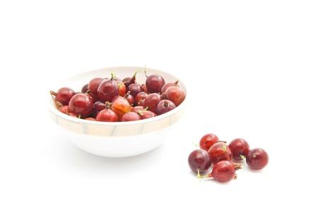 gooseberries: red gooseberries on a dish on white