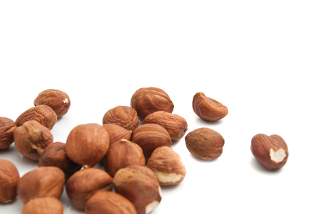 heap of delicious hazelnuts on white background