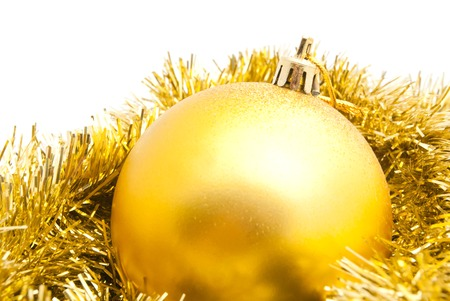 the tinsel: christmas tree toy and gold tinsel closeup on white