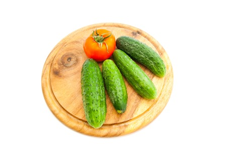 tast: cucumbers and tomato on cutting board on white