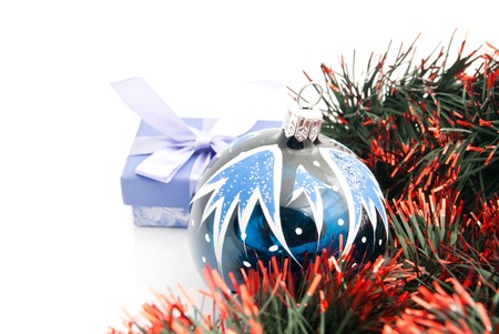 blue gift box: christmas tree toy, blue gift box and tinsel on white background