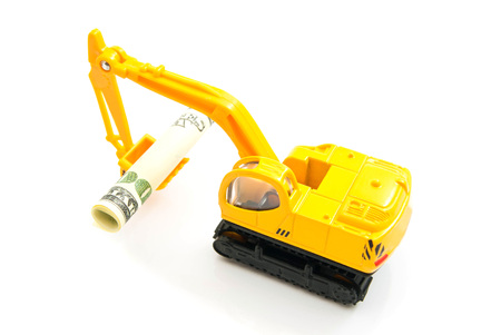 auto leasing: dollars banknotes and yellow backhoe on white closeup