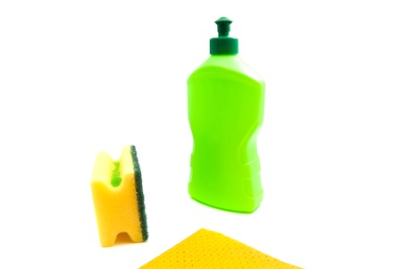 sponge, rag and green bottle on white