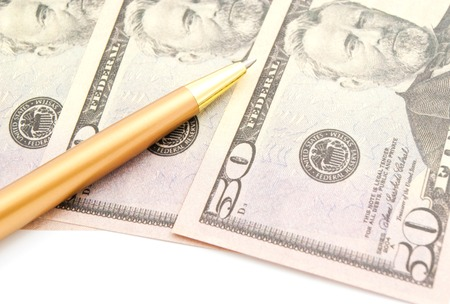 dollars banknotes and golden pen on white