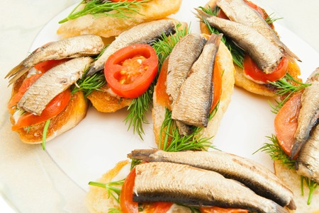 sprats: some sandwiches with sprats on a dish on white