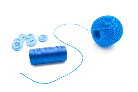 cotton thread: blue spools of thread and buttons on white background