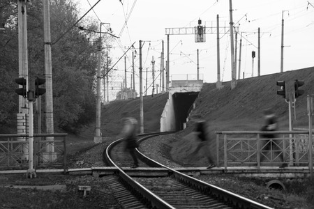 black and white railroad tracks: people pass the railroad tracks in city black and white