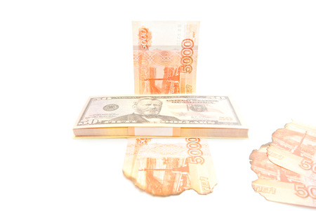 pack of dollars: pack of dollars and burnt rubles on white closeup Stock Photo