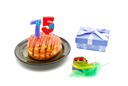 five years': donut with seventy five years birthday candle, whistle and gift on white