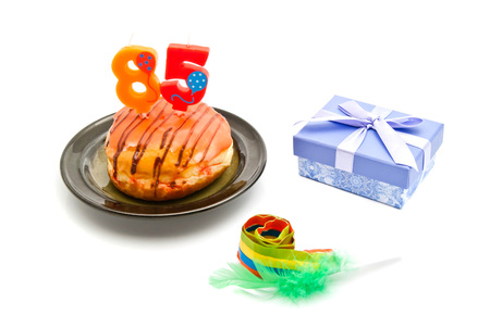 five years': donut with eighty five years birthday candle, whistle and gift on white background