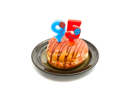 five years': donut with ninety five years birthday candle on white Stock Photo