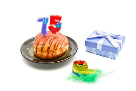 five years': donut with seventy five years birthday candle, whistle and gift on white background