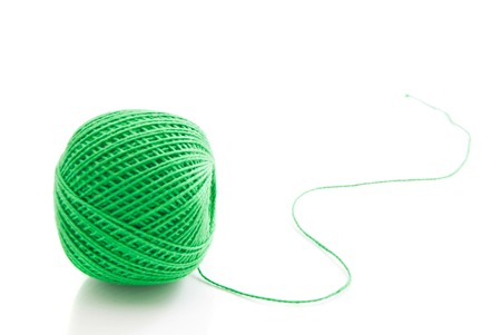 spool of green thread on white background closeup