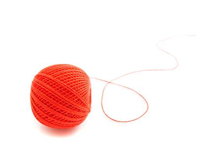 hilo rojo: carrete de hilo rojo de cerca en blanco Foto de archivo