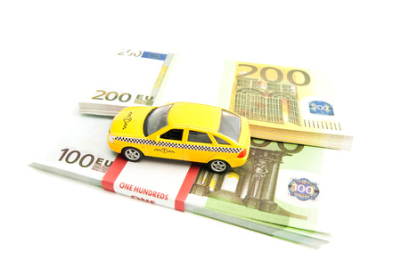 afford: yellow taxi car and banknotes on white background Stock Photo