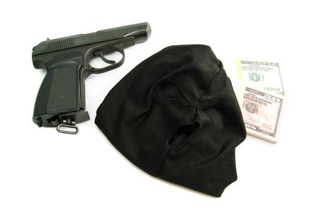 gunshot: mask, gun and dollars on white background closeup