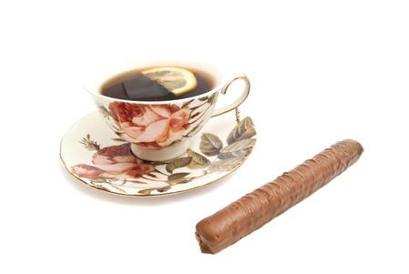 coffeecup: cup of tea with lemon and chocolate bar on white closeup