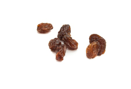 snacking: many delicious raisins closeup on white background
