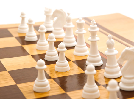 Chess on a chessboard on white background closeup