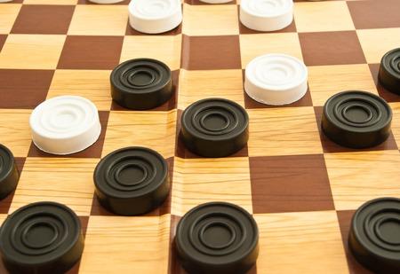 checkers: plastic white and black checkers on a board