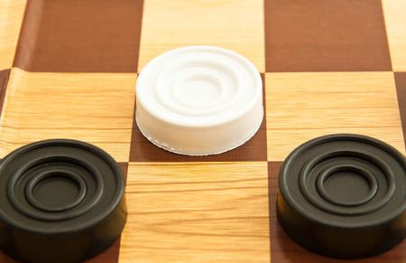checker: white and black plastic checkers on a board Stock Photo