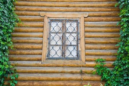 rejas de hierro: ventana detrás de barras de hierro en una pared de madera