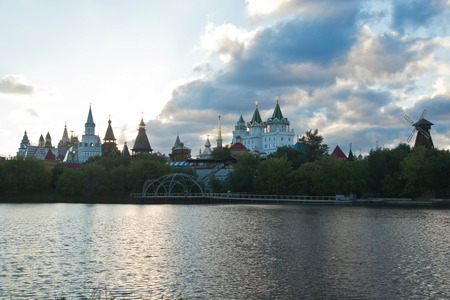 wooden mill and Kremlin on the banks of the river in evening