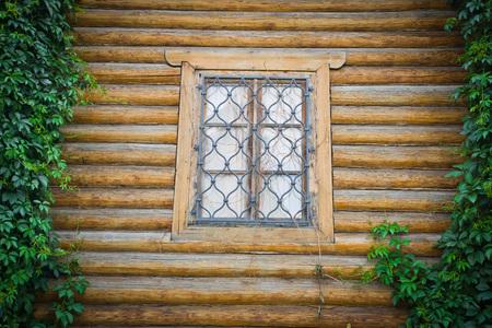 rejas de hierro: window behind iron bars on wooden wall Foto de archivo