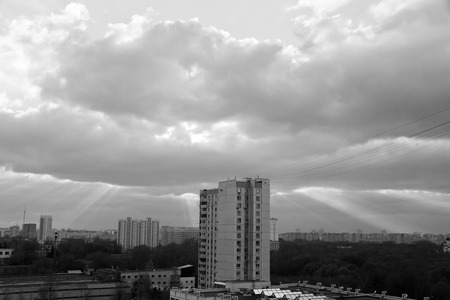 sunbeams breaking through the clouds in city black and white