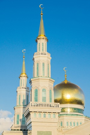 mosque with gold domes against the blue sky