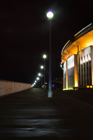 stadium and street lamps in city at night