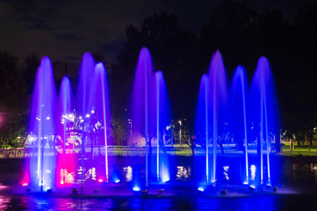 Fountain with backlight on the pond in night park