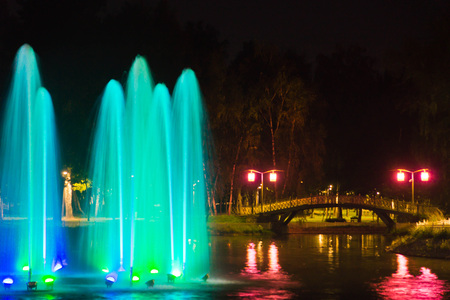 Fountain with backlight on pond in the park Stock Photo
