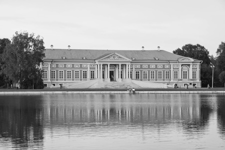 old manor house from the shore of pond black and white