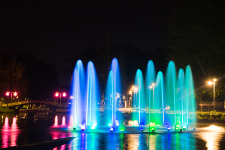 Fountain with backlight on the pond in park Stock Photo