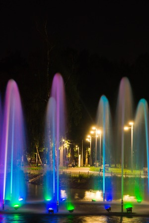 Fountain with backlight on the pond in the park