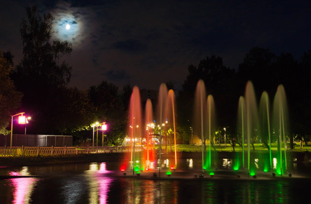 Fountain with backlight on the pond in evening park Stock Photo