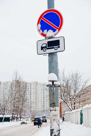 road signs under the snow near the road and buildings