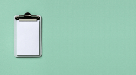 Clipboard on turquoise horizontal background. Flat lay, top view trendy for banner