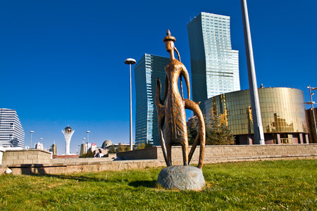 spellbinding: A statue on the background of skyscrapers, green grass and clear blue sky