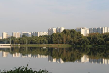 Multi-storey residential district in Moscow city on the bank of the river with reflection in it