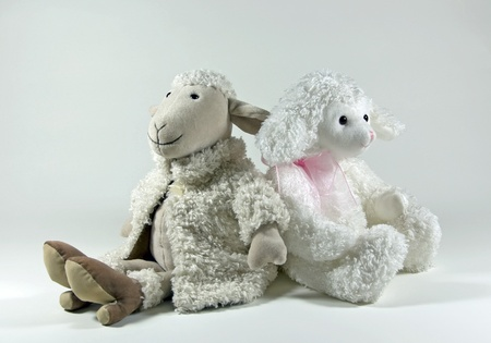 Two toy lambs, one dressed in high heels and a coat and the other dressed in a pink ribbon