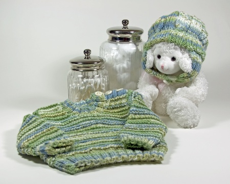 A babys hand knit sweater and matching hat on a toy lamb along with cotton balls and Q-tips in apothecary jars