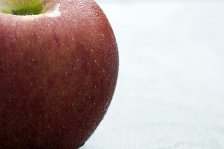 A photograph of a whole nutritious dewy crisp red apple