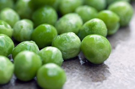 A photograph of bright dewy fresh shelled green peas Stock Photo