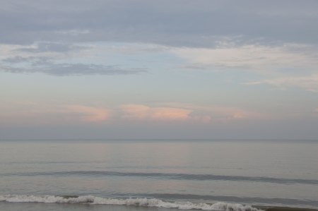 Calm and quiet surf on an empty beach with pink and blue clouds in the background