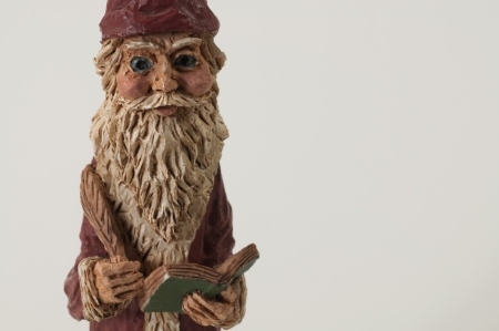 Carved figure of Santa Claus holding a book and a quill pen