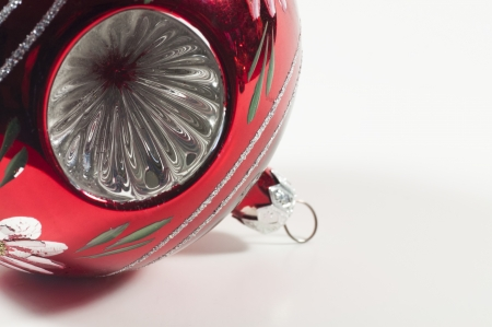 A red ball Christmas tree ornament with crinkled circular metal indentations