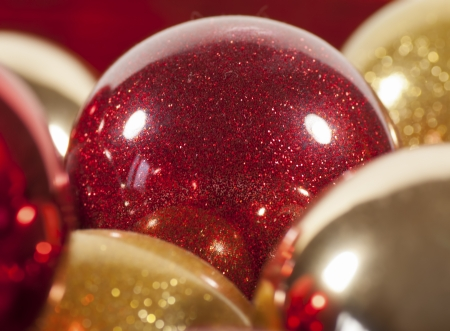 A red sparkling Christmas ball nestled among other gold and silver balls
